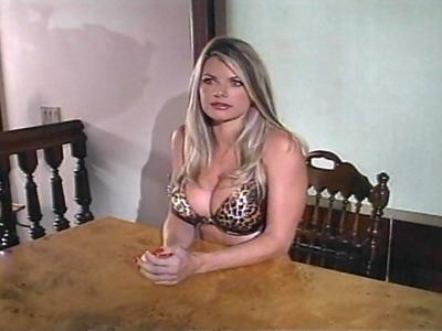 Katie, superbe blonde aux gros seins vêtue de dessous léopard, est assise à tabl